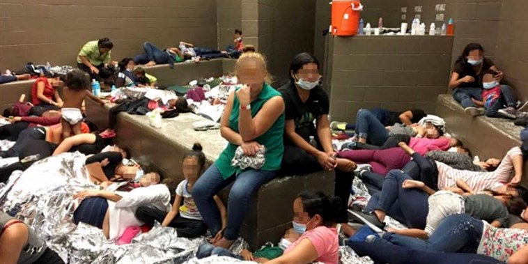 'Help': Photos show hundreds of migrants squashed into cells, appealing for assistance