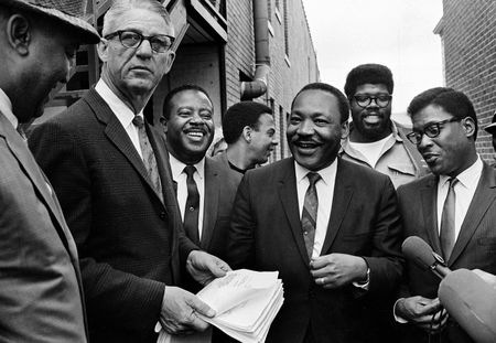 Martin Luther King Jr., center, and Rev. Ralph Abernathy, third from left, share a laugh outside court in Decatur, Ga., Oct. 25, 1960. Others are unidentified. Andrew Young is seen at center, facing right. (AP Photo)