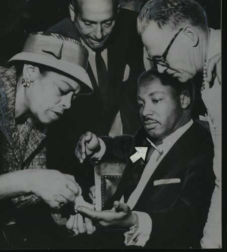 Martin Luther King gets first aid in Harlem store after he was stabbed in 1958. Friends wrap finger, leave weapon sticking in chest. (Removal of weapon might have caused fatal hemorrhage)