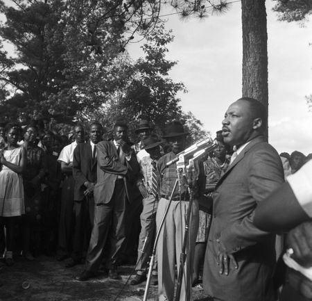 Martin Luther King Jr. addressing an audience at a voter rally in a wooded area in Alabama.